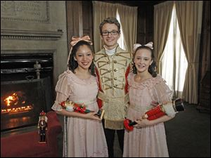 Cairo Gere, 17, center, who plays the nutcracker, has his picture taken with