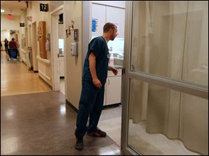 ER tech Matt Waller talks to a patient in a private room at the Toledo Hospital Emergency Room.