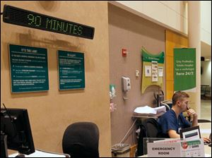 ER tech Brandon Bauman works the registration desk at the Toledo Hospital Emergency Room, where a sign behind him lets patients know there is a 90-minute wait.