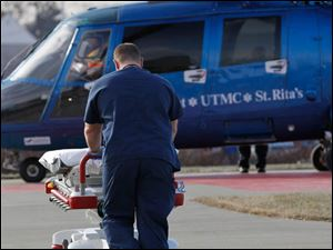 Paramedic Brian Mullins wheels a bed to the Life Flight helicopter bringing in a car accident victim to the University of Toledo Medical College ER.