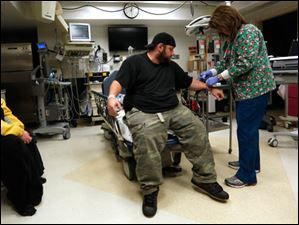 Rebecca Wilkes, left, watches as her boyfriend Tony Collins gets his IV tube removed by RN Jane Reeder at the Mercy St. Vincent Emergency Center.