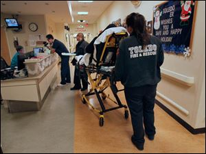 Toledo Fire & Rescue workers transport a patient to the Toledo Hospital Emergency Room.
