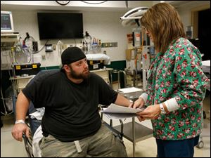 Tony Collins is checked out by RN Jane Reeder at the Mercy St. Vincent Emergency Center.