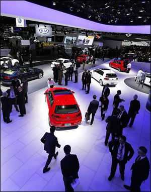 Volkswagens and Kias are on display at the North American International Auto Show in Detroit.