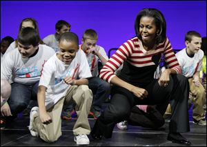 First lady Michelle Obama does the Interlude dance with kids on stage during a Let's Move event with children from Iowa schools, at the Wells Fargo Arena in De Moines, Iowa, in February, 2012.