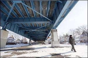 John Whitlow, outreach technician, looks around the Anthony Wayne Bridge for homeless people who need food and shelter in order to bring them to a safe place.