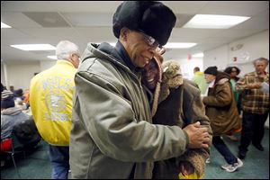 John Whitlow, outreach technician, left, hugs former client Velma Trotter, right, while he was visiting St. Paul's Community Center.