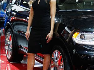 A model stands next to a Dodge Durango.
