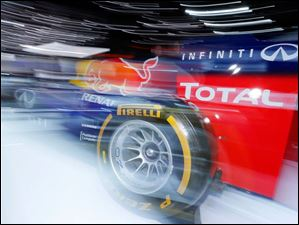 A slow shutter speed makes the Infiniti Red Bull Formula One car appear to be streaking through the auto show.