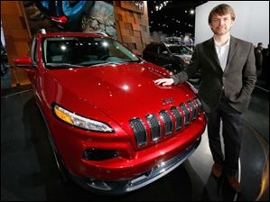 Jeep CEO Mike Manley stands next to a new Cherokee.