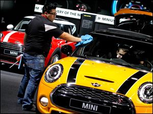 Show worker Emanuel Cuevas cleans off a Mini Cooper S.
