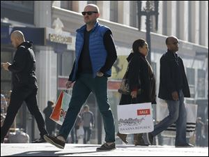 Last minute holiday shoppers carry bags as they cross the street in San Francisco on Christmas Eve.