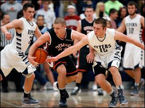 Lake's Cody Witt (15) and Connor Bowen (32) defend against Otsego's Cody Downs (22).