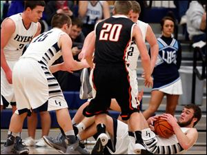 Lake's Todd Walters (10) comes up with a loose ball against Otsego's Schyler Scherff (20).