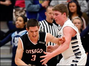 Lake's Jacob Rettig (22) defends against  Otsego's Jalen Myers (3).