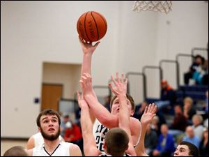Lake's Jacob Rettig (22) shoots against Otsego's Schyler Scherff (20).
