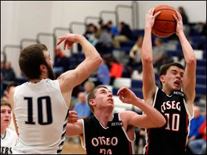 Otsego's Josh Horseman (10) pulls in a rebound against Lake's Todd Walters (10).
