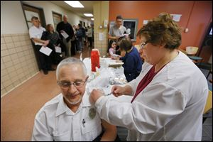 Tom Taddonio, a fire inspector, gets a flu shot from nurse Cindy McLeod at the Toledo-Lucas County Health Department. The immunization event drew more than double the normal amount of people Wednesday.