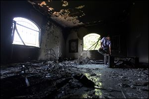 This Sept 13, 2012 file photo shows a Libyan man investigating the inside of the  U.S. Consulate in Benghazi, Libya, after an attack that killed four Americans.