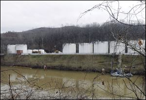 Workers, left, inspect an area outside a retaining wall around storage tanks Monday where a chemical leaked into the Elk River at Freedom Industries storage facility in Charleston, W.Va.