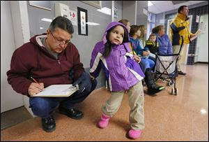Donald Martinez fills out a form for his granddaughter Emilia Martinez, 4, as they wait in line to get a flu shot. The county health department will have another flu immunization clinic on Saturday.