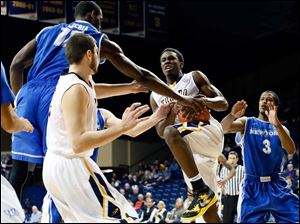 Toledo guard Justin Drummond (4) pulls in a rebound against Buffalo forward Javon McCrea (12).