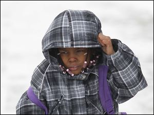 Jordyn White, 6, tries to keep warm as she walks along Michigan Avenue and home from Horizon Science Academy.