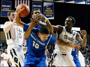 Toledo guard Justin Drummond (4) battles against Buffalo guard Jarryn Skeete (10) and Justin Moss (10) for a rebound.