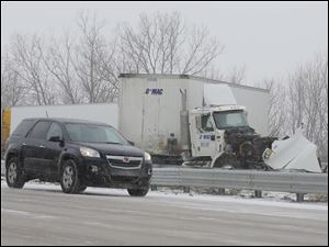 A northbound car moves slowly past a jack knifed truck on southbound I-75 near Bay Creek Road in Erie, Mi., following an accident.