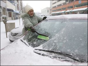 Liz Geniac works to brush the snow off of her car on North Superior Street near Madison as she leaves one job to head to another.