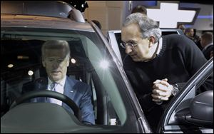 Vice President Biden sits in a Chrysler product and listens to Chrysler-Fiat CEO Sergio Marchionne at the auto show.