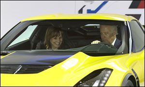 Vice President Biden and General Motors CEO Mary Barra sit in a Corvette Stingray during a tour of the auto show.