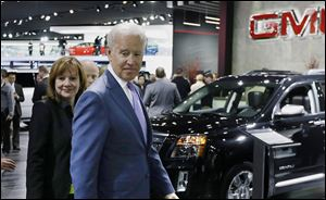 Vice President Joe Biden and Mary Barra, General Motors' chief executive officer, look over the GM display during a tour of the North American International Auto Show in Detroit.
