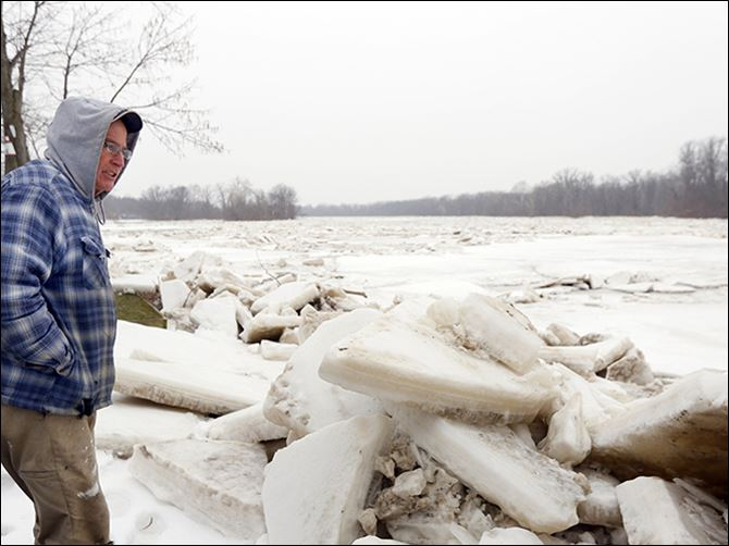 n6jam-3 Brett Gillespie looks over the ice jam behind his Wood County home on the Maumee River, off State Rt. 65 near Range Line Road.