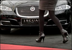 A woman passes by a Jaguar XJ during an Auto Moto Show in Bucharest, Romania.