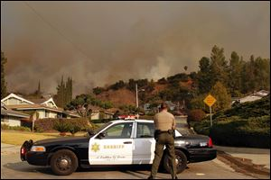 An Los Angeles County Sheriff blocks a road in a neighborhood while a wildfire burns in the hills just north of the San Gabriel Valley community of Glendora, Calif.
