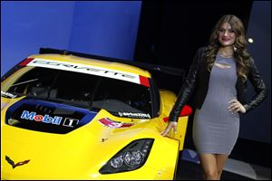 A model poses with a Corvette race car at the North American International Auto Show in Detroit, Monday.