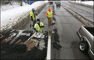 Corey Allison, Paula Williams, and Dwayne Garrett, from left, patch potholes on Berdan Avenue near Detroit Avenue last week.