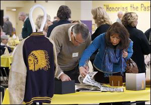 Waite alumnus Jim Ellinger and his wife, Nancy, of Holland glance through yearbooks during the centennial celebration.
