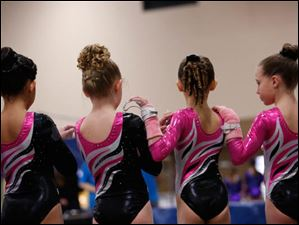 GymQuest (Beavercreek, Ohio) gymnasts wear their wrist gear as they stand for the National Anthem.