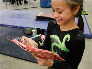 Sunrise's Madison Soleau, 10, smiles as she logs her strong uneven bar score.