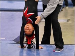 Toledo Turners gymnast Genevieve Thomas is assisted on her handstand by coach Kristin McGee during the Battle of Champions event at the SeaGate Convention Center in Toledo.