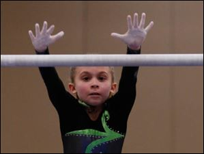 Sunrise's Cali Mitchey, 8, changes bars in the uneven bars.
