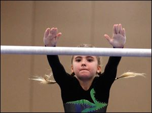 Sunrise's Libby Boisselle, 9, changes bars in the uneven bars.