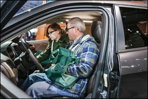 Andrew Gierak, behind the wheel, and his daughter Anna Gierak of Leonard, Mich., examine a 2014 Jeep Cherokee. Mr. Gierak was impressed with the SUV.