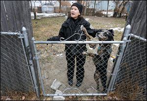 Nancy Schilb speaks with an owner as she pets his dog during an investigation earlier this month.
