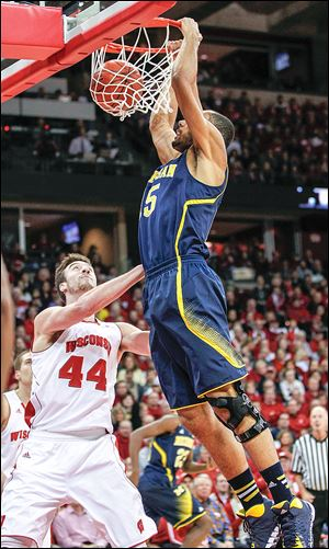 Michigan's Jon Horford, right, dunks over Wisconsin's Frank Kaminsky during the first half of their Big Ten Conference game.