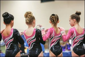 Members of the GymQuest team of Beavercreek, Ohio, stand for the national anthem  at the SeaGate Convention Centre during Saturday's all-female gymnastics competition.