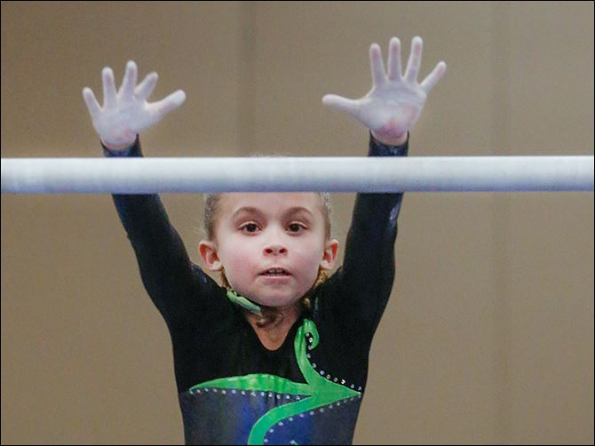 19n1uneven-2 Cali Mitchey, 8, changes bars in the uneven  bars. Unlike h