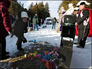 Lucy Bell of Toledo lays a flower at the
